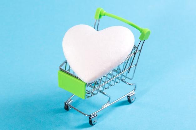 青いスペースに買い物かごの中の白いハート。愛を買い、心を買いなさい。