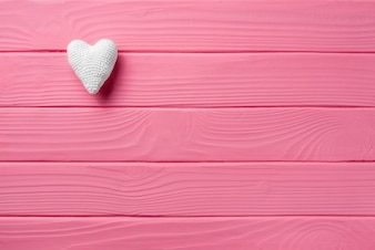 White heart on a pink wooden background, Valentine's Day concept