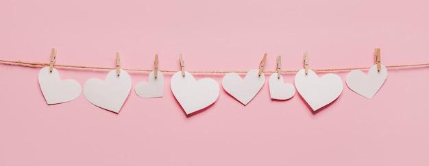 격리 된 분홍색 배경, 사랑과 발렌타인 개념에 밧줄에 흰색 하트 핀