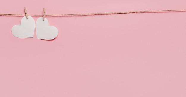 孤立したピンクの背景、愛とバレンタインの概念のロープ上の白いハートピン