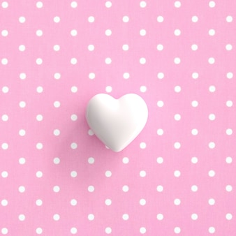 White heart on pokadot pink background. minimal valentine concept idea.