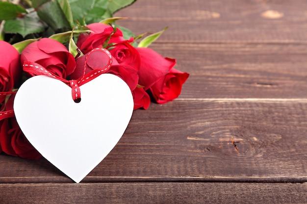 Tag cuore di san valentino e le rose sulla tavola di legno