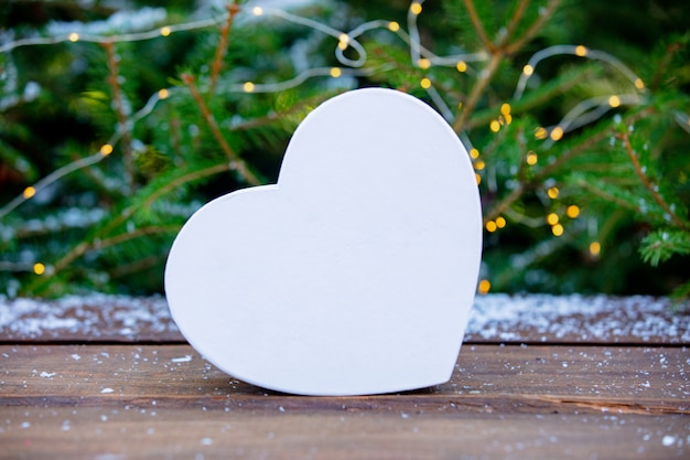 White heart shape box on wooden table with fairy lights and pine tree
