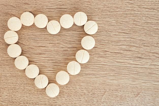Форма белого сердца из таблеток для терапии, концепции лечения и здравоохранения на фоне aqua menthe. таблетки для любителей потенции крупным планом, болезнь сердца. медицинский баннер, копия пространства