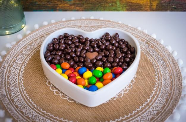チョコレートで覆われた茶色とカラフルなチョコレート、ヘーゼルナッツ、アーモンドで満たされた白いハート型のボウル