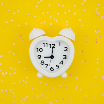 White heart shaped clock on yellow background