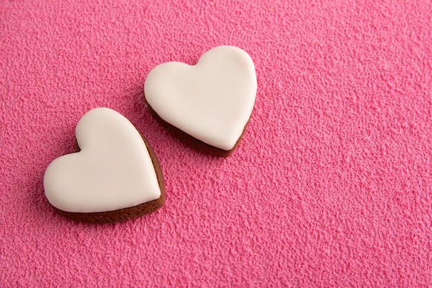 White heart shaped cookies on pink background. mothers day. women's day. valentines day.