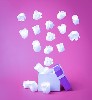 White heart-shaped rose buds fly out of the gift box. the concept of love.