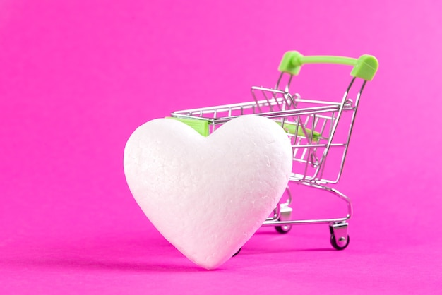 White heart next to a shopping basket on a pink space. buy love, buy heart.