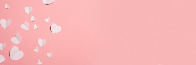 ピンクの背景に紙から切り取った白いハート。バレンタインデーの構成。バナー。フラットレイ、上面図。