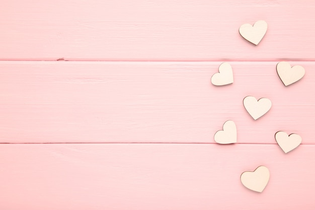 White hearts on a pink background. wooden hearts