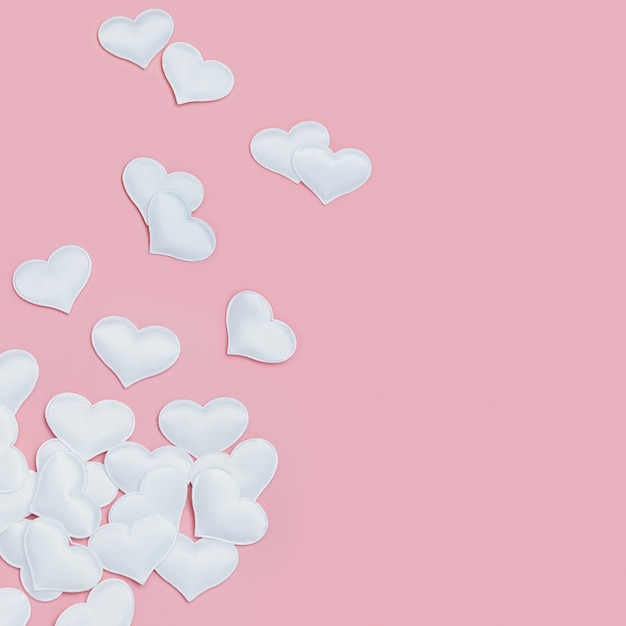 White hearts symbols of love on pink fon holiday background for valentines day