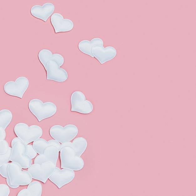 バレンタインデーのピンクのフォンの休日の背景に愛の白いハートのシンボル