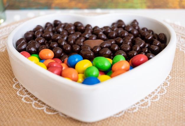 茶色とカラフルなチョコレートヘーゼルナッツとアーモンドで満たされた白いハート型のボウル