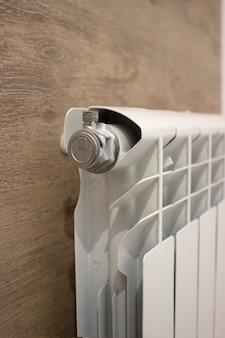 Белый радиатор отопления обогревает комнату. радиатор отопления, белый радиатор в квартире.