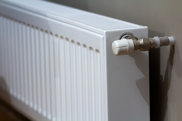 White heating radiator with thermostat valve on wall in an apartment interior after renovation works.