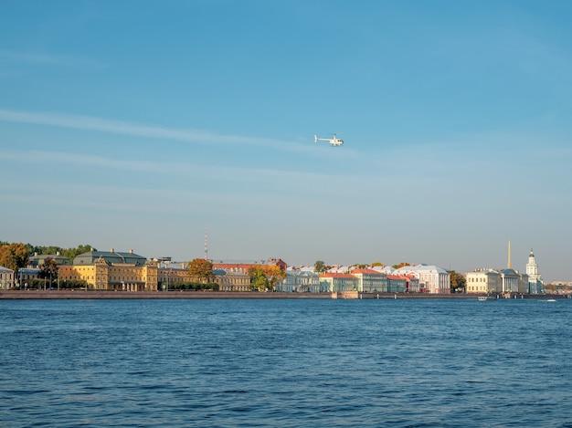 Белый вертолет пролетает над невой в санкт-петербурге.