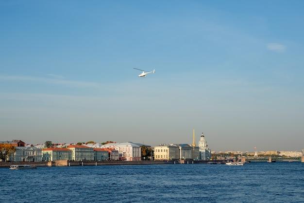 Белый вертолет над голубой рекой. санкт-петербург.