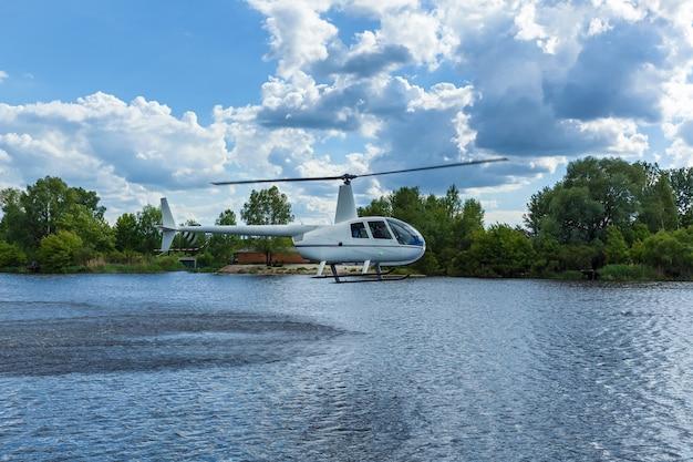 하늘과 나무에 물 위에 흰색 헬리콥터. 물 위에 헬리콥터입니다.