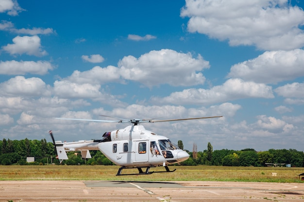 A white helicopter takes off from the runway