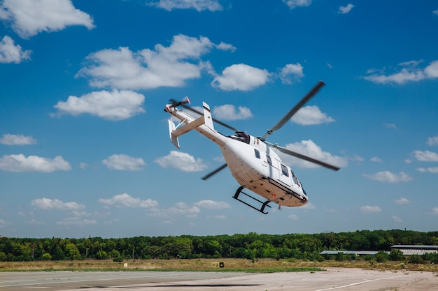A white helicopter takes off from the runway.