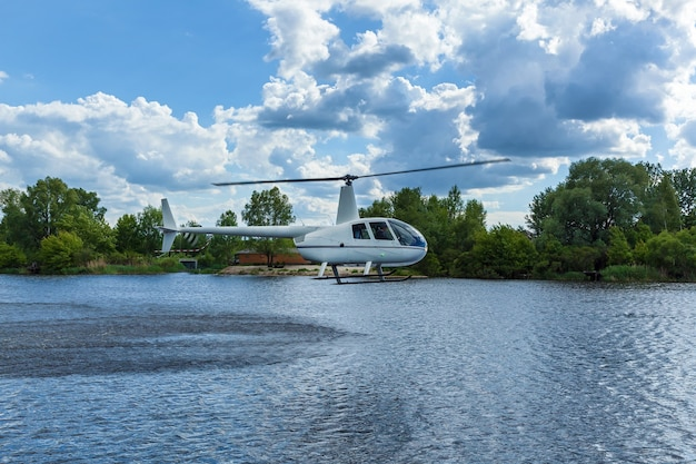 White helicopter over water against the sky and trees. helicopter over water.