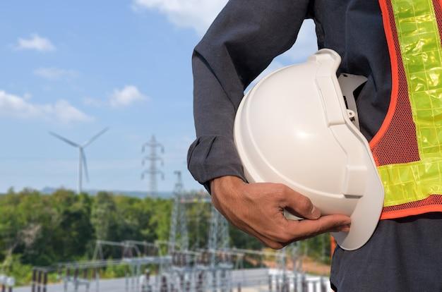 白いヘルメットは、風力タービン発電所の背景にある電気技師の手にあります。
