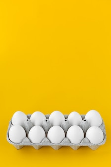 White hen eggs in open cardboard carton on yellow background