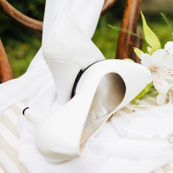 White high heels over the scarf on white table