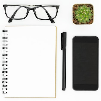 White hipster desk with notebook, pen, smartphone and eyeglasses.