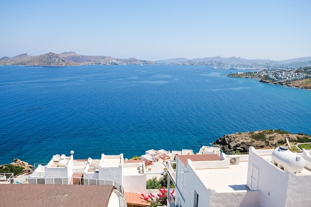 White holiday villas houses on resort with sea view and palm trees and view to city.