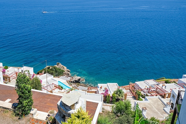 White holiday villas houses on resort with sea view and swimming pool and palm trees.