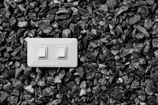 A white home electrical light switch on a gravel.