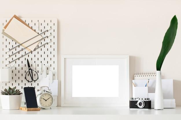 White home office desk with photo frame, supplies, flower. minimal blank frame mockup design.