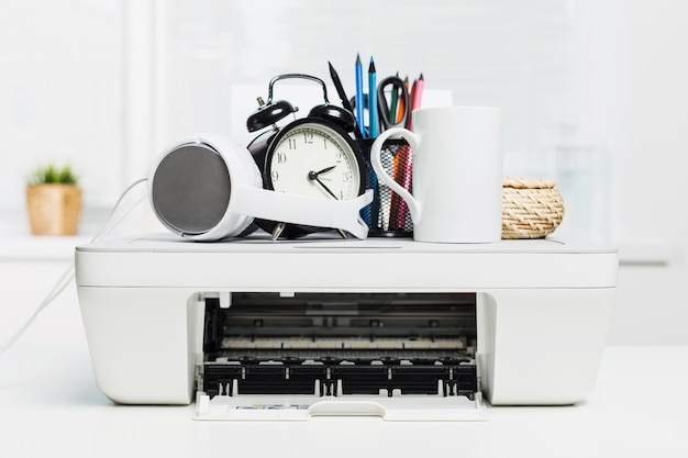 White home printer and white headphones on office table
