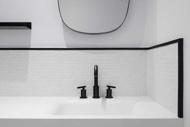 洗面台の鏡と黒い蛇口が付いている白いハニカムタイルの浴室