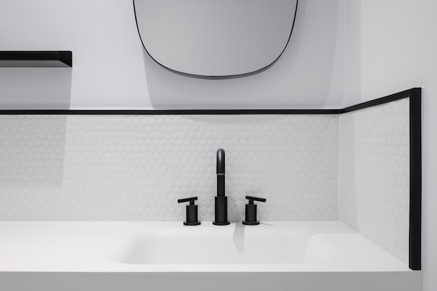 White honeycomb tile bathroom with wash basin mirror and black faucet