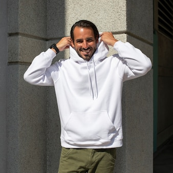 White hoodie on man with green pants in the city