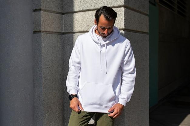 Белая толстовка с капюшоном на мужчине с зелеными штанами в городе