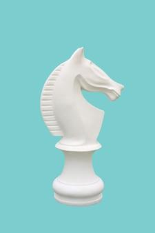 シアンの背景に分離された白い馬のチェス