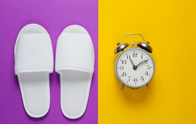 White hotel sleeping slippers and alarm clock on colored surface.