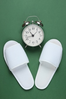 White hotel sleeping slippers and alarm clock on green surface.