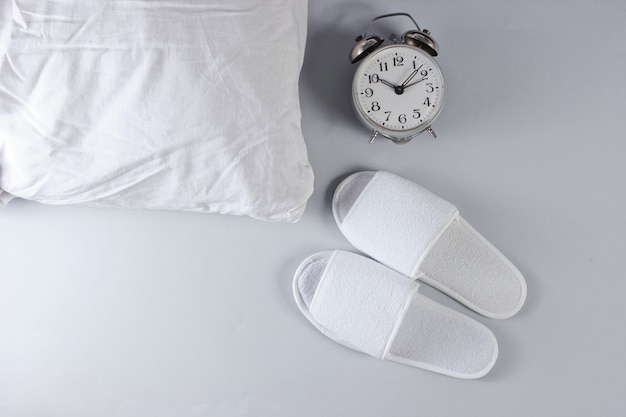White hotel sleeping slippers, alarm clock and pillow on gray surface.
