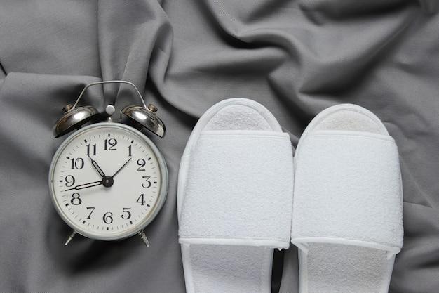 白いホテルのスリッパと灰色のベッドカバーの目覚まし時計。
