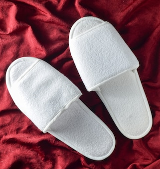 White hotel slippers on a red mat. top view.