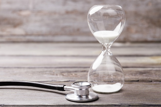 흰색 모래 시계와 청진 기. 평생 및 노화 개념.