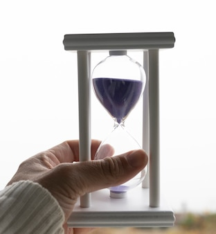 A white hourglass with purple sand