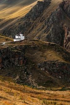 山に囲まれた白い家、垂直方向のビュー。美しい秋の風景。秋の風景の形でスマートフォンのスクリーンセーバー。山の中の小さな家。秋の山。