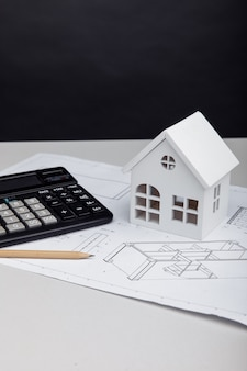 White house and calculator on architectural project. house building costs concept. vertical image