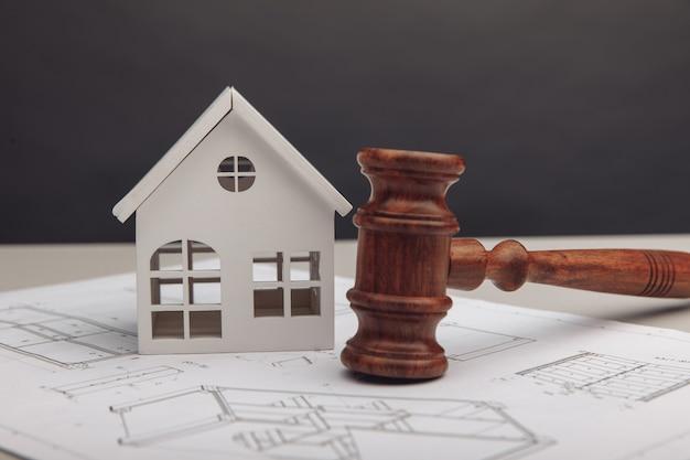 白い家、絵を描いて、テーブルの上にガベルを審査します。法律と建設の概念。